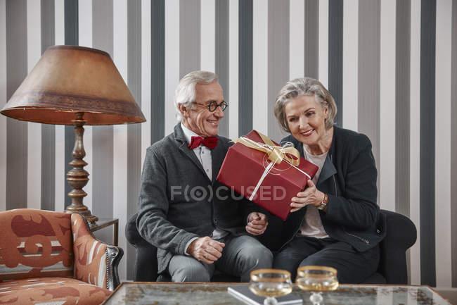 Щаслива пара старший, сидячи на дивані з подарунок — стокове фото