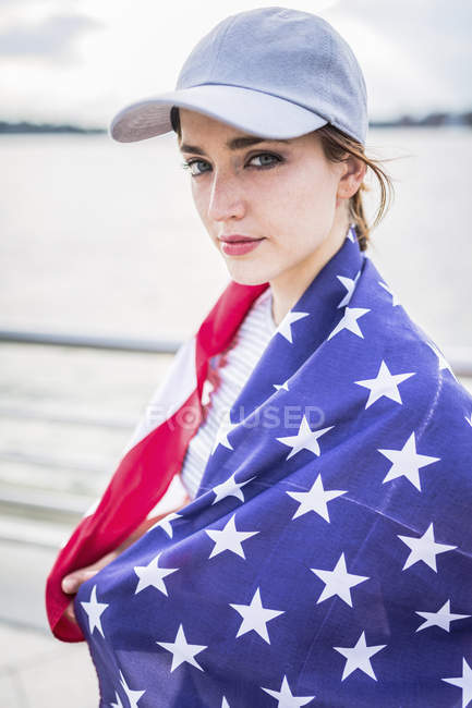 Portrait of woman with baseball cap and American flag — Stock Photo
