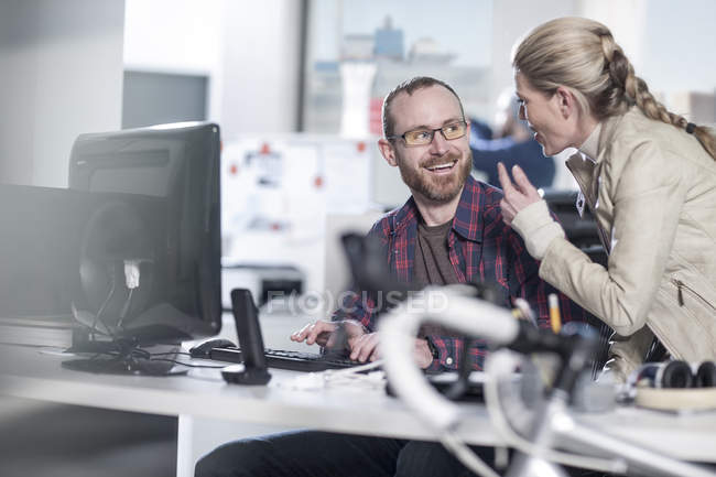 Two casual office workers having informal meeting in office — Stock Photo