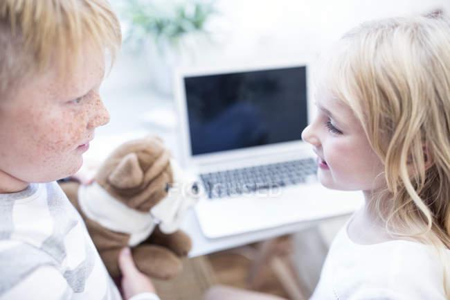 Hermano y hermana con peluche mirando delante del ordenador portátil - foto de stock