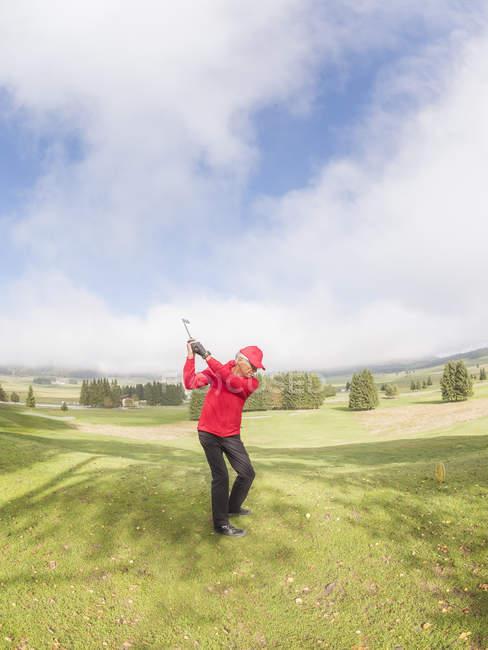 Italien, Veneto, Dolomiten, Golfer spielen auf Golfplatz, bewölkt sonnige Landschaft mit grünen Rasen auf Hintergrund — Stockfoto