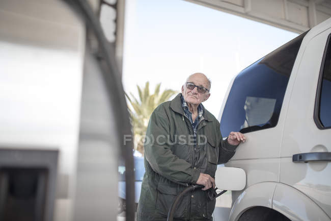Elderly man fueling car at gas station — Stock Photo