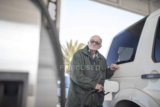 Personnes âgées homme voiture de ravitaillement à la station d'essence — Photo de stock