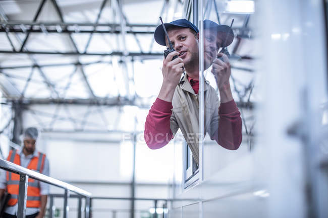 Worker with walkie-talkie instructing in factory — Stock Photo