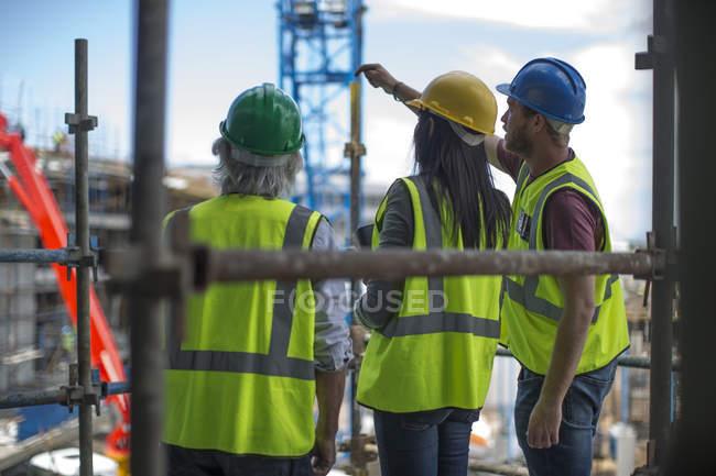Працівник будівництва говорити з чоловіком і жінкою на будмайданчику — стокове фото