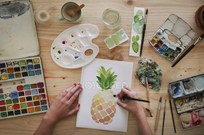 Woman's hand painting aquarelle of a pineapple on desk in her studio — Stock Photo