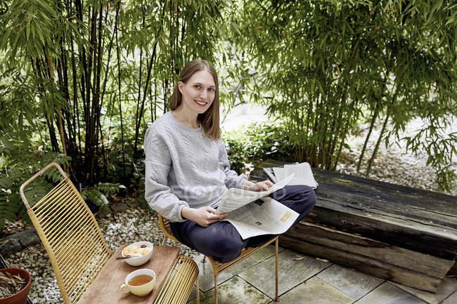 Mulher sorridente no terraço ler jornal — Fotografia de Stock
