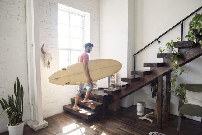 Jeune homme portant une planche de surf dans les escaliers d'un loft — Photo de stock