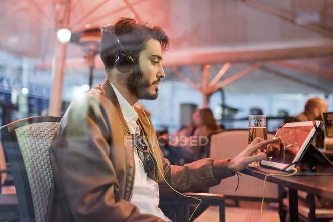 Young man with headphones using tablet at outdoor bar — Stock Photo