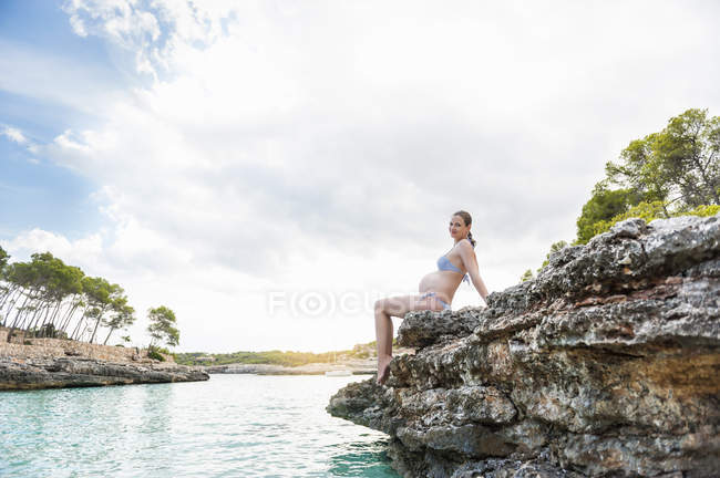 Pregnant woman sitting on rock at sea — Stock Photo