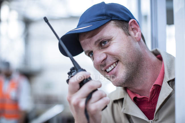 Smiling worker with walkie-talkie in factory — Stock Photo