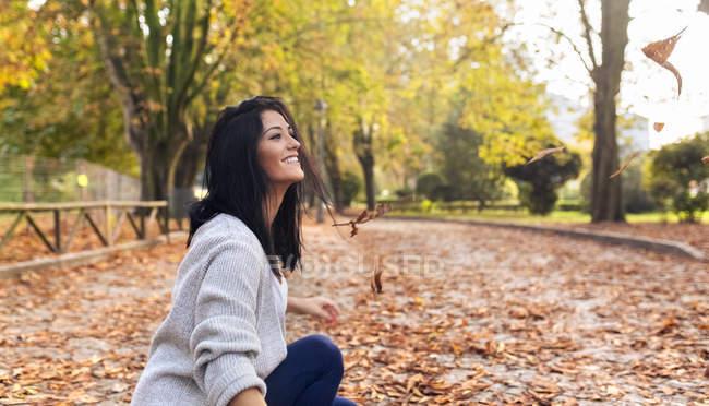Feliz joven jugando con hojas en un parque en otoño - foto de stock