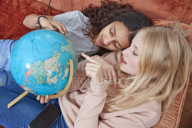Two girls lying on couch pointing at globe — Stock Photo