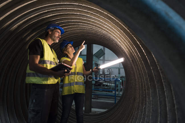 Man and woman examining giant construction tube — Stock Photo