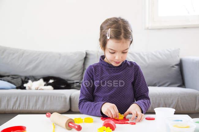 Petite fille découpe pâte à modeler — Photo de stock