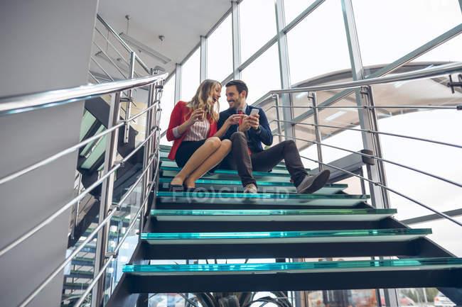 Два деловых людей, сидя на лестницы с помощью мобильного телефона — стоковое фото