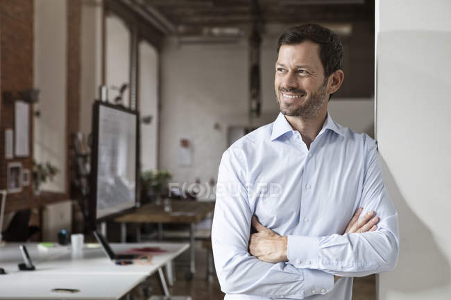 Portrait of smiling businessman standing in office with arms crossed — Stock Photo