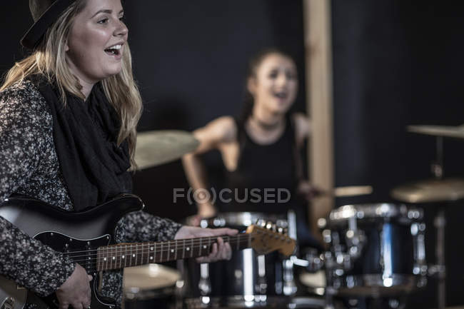 Female rock guitarist and drummer at recording studio — Stock Photo