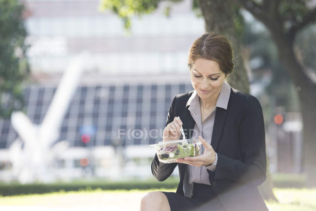 Portrait of businesswoman eating salad in park, Los Angeles — Stock Photo