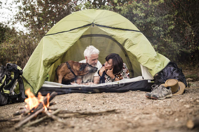 Senior couple with dog lying in tent at campfire — Stock Photo
