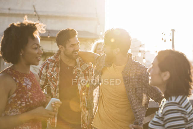 Friends at rooftop party in sunset light, Los Angeles, USA — Stock Photo