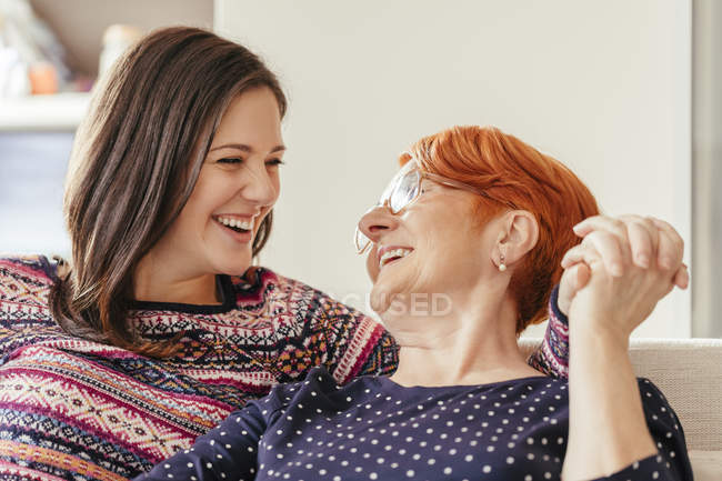 Mother and adult daughter smiling to each other sitting on couch — Stock Photo