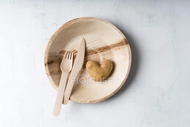 Картофель в форме сердца и деревянная вилка и нож на пластине пальмового листа — стоковое фото