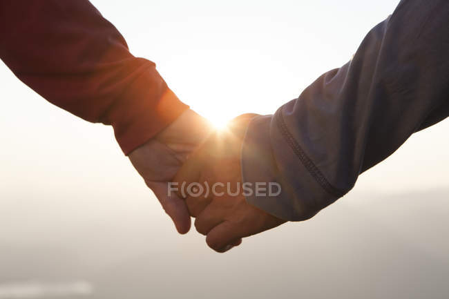 Couple hand in hand at sunset — Stock Photo