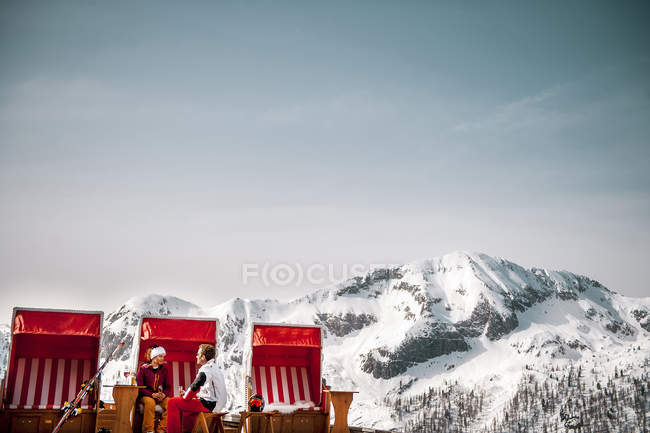 Austria, Altenmarkt-Zauchensee, couple sitting at hooded beach chair in the mountains — Stock Photo