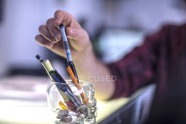 Man's hand taking pencil, close-up — Stock Photo
