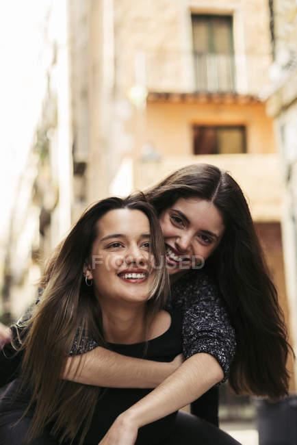 Portrait of two happy best friends hugging in city — Stock Photo