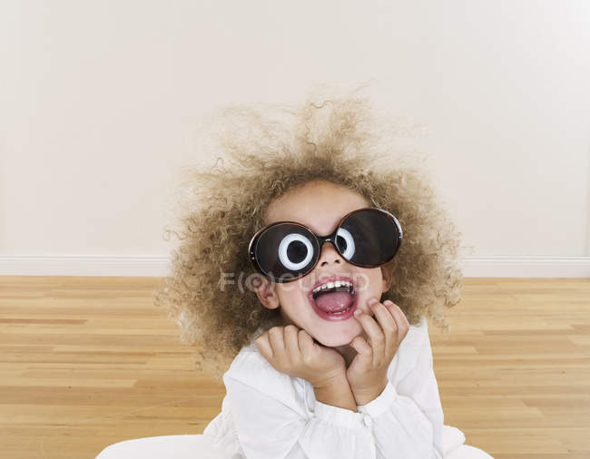 Portrait of smiling girl with blond ringlets wearing oversized sunglasses — Stock Photo