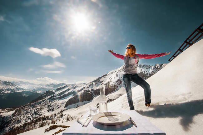 Young woman standing in the mountains, with laid table in foreground — Stock Photo