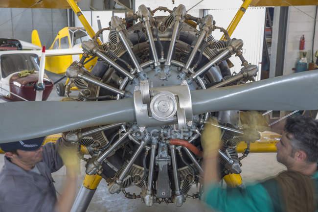 Mechanics in hangar repairing light aircraft — Stock Photo