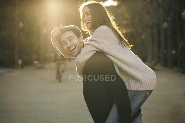 Pareja divirtiéndose juntos en un parque al atardecer - foto de stock