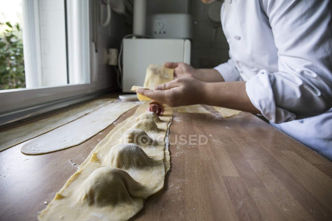 Man preparing handmade raviolis in kitchen — Stock Photo
