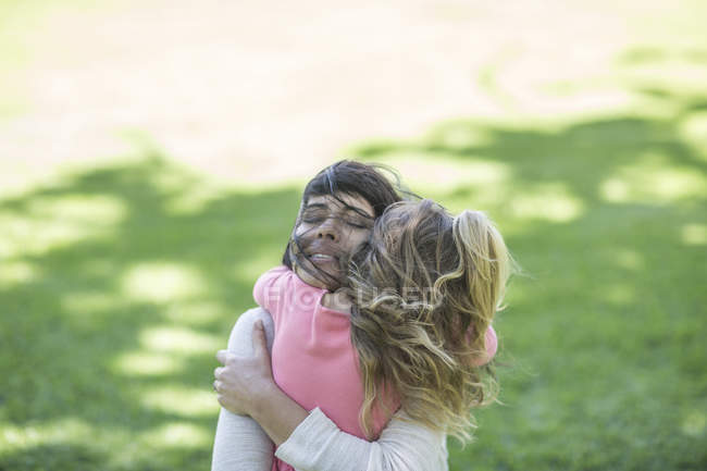 Mother hugging daughter at green park — Stock Photo