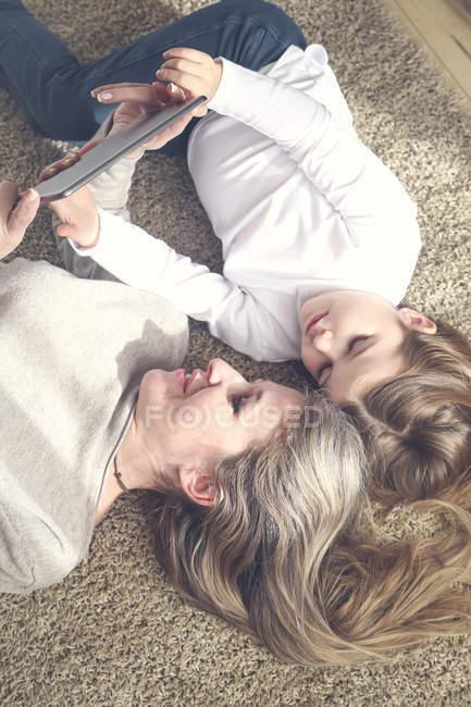 Mère et fille couché sur le tapis et à l'aide de tablette — Photo de stock