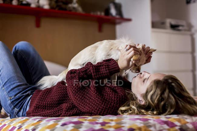 Mulher deitada na cama brincando com seu cachorro — Fotografia de Stock