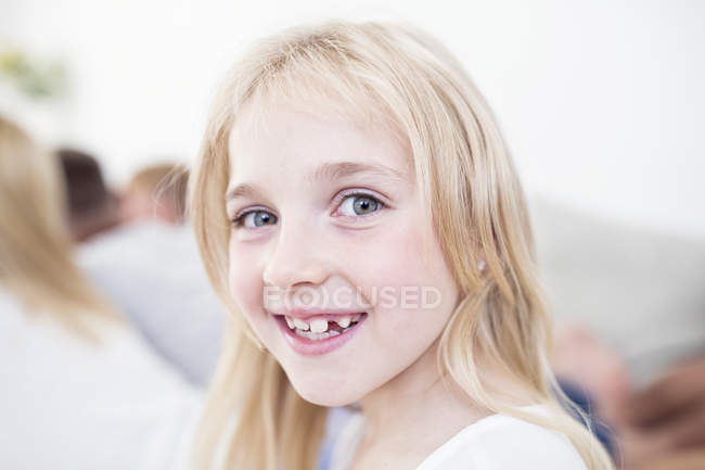 Portrait of smiling blond girl with family on background — Stock Photo
