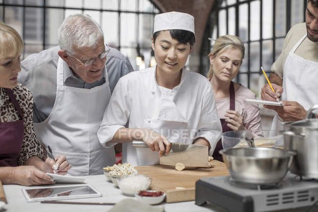 Chef ready to chop food in cooking class — Stock Photo