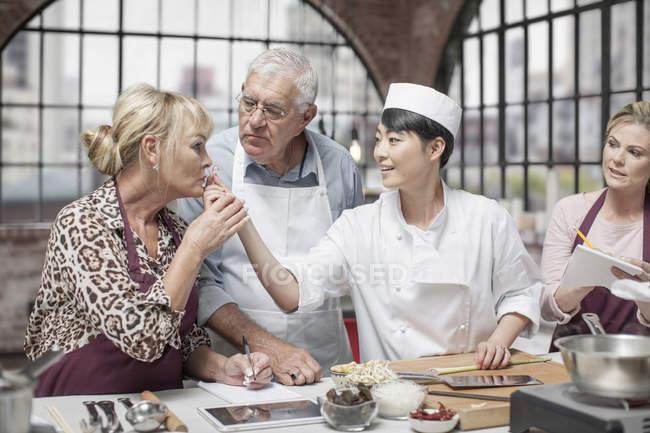 Erwachsene Schüler riechen Sellerie im Kochkurs — Stockfoto