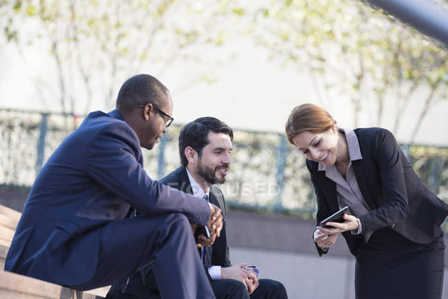Smiling business people sharing tablet outdoors — Stock Photo