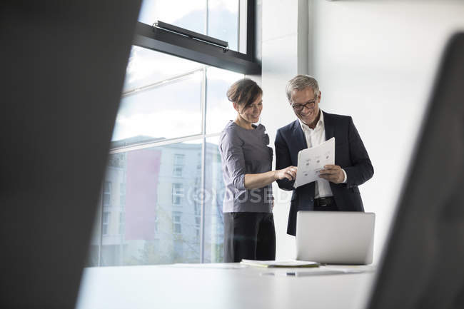 Businessman and businesswoman discussing documents — Stock Photo