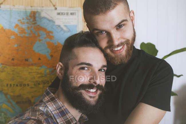 Porträt eines glücklichen homosexuellen Paares, das in die Kamera blickt — Stockfoto