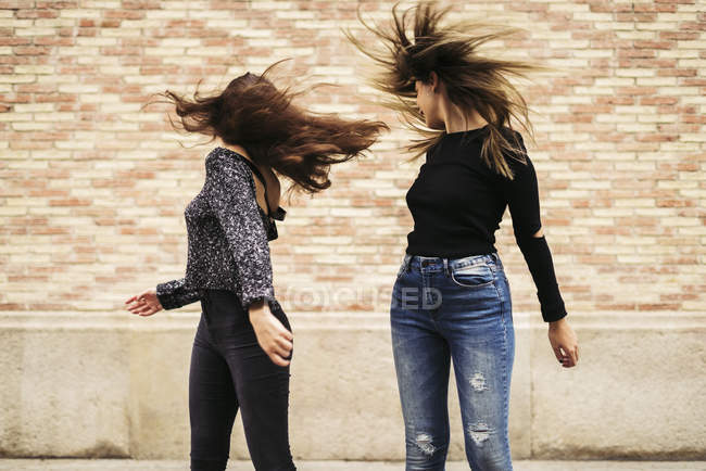 Two happy women tossing long hair — Stock Photo