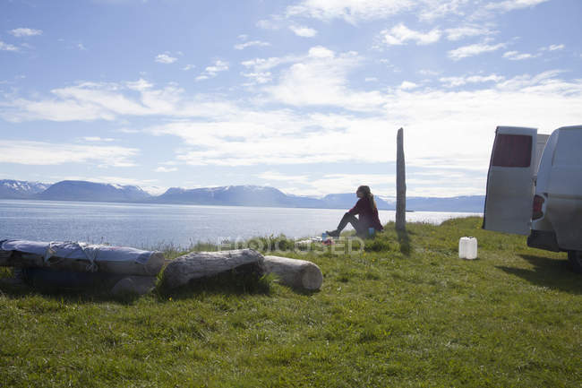 Iceland, woman sitting on grass and looking at view in nature next to van — Stock Photo