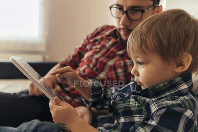 Père et fils assis sur le canapé avec tablette numérique — Photo de stock