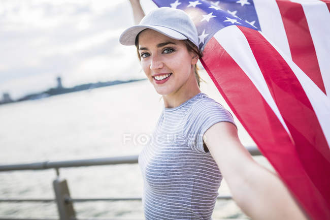 Portrait of smiling woman in baseball cap with American flag — Stock Photo