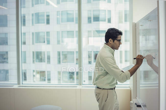 Focused businessman writing on whiteboard in office — Stock Photo